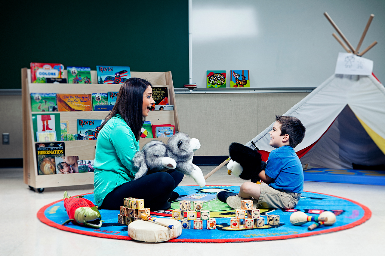 Ravina Dhaliwal sits with a child on mat surrounded by toys