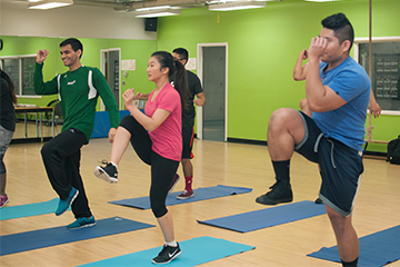 students in a fitness class kicking one leg up