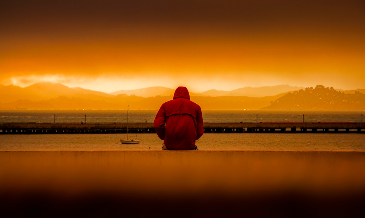 man sits near water