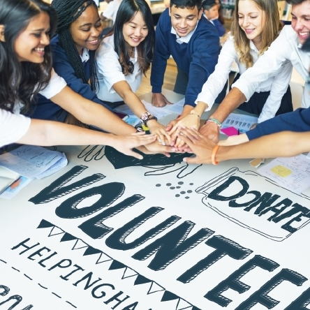 "Young adults of various ethnicity put their hands together over a black and white poster that says ""Donate"" and ""Volunteer"""