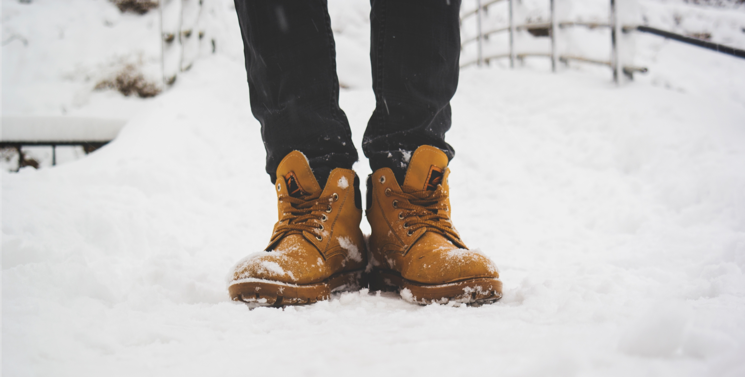 Picture of legs and feet in brown boots, standing in snow